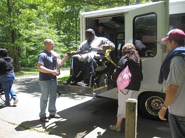 A student in a wheelchair uses the lift to exit the bus during an IAGD field trip.