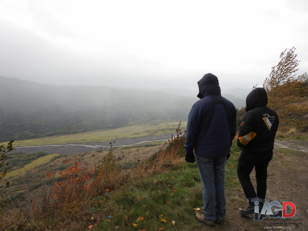 Two people in coats with their hoods up look out over a foggy river valley from high ridge.