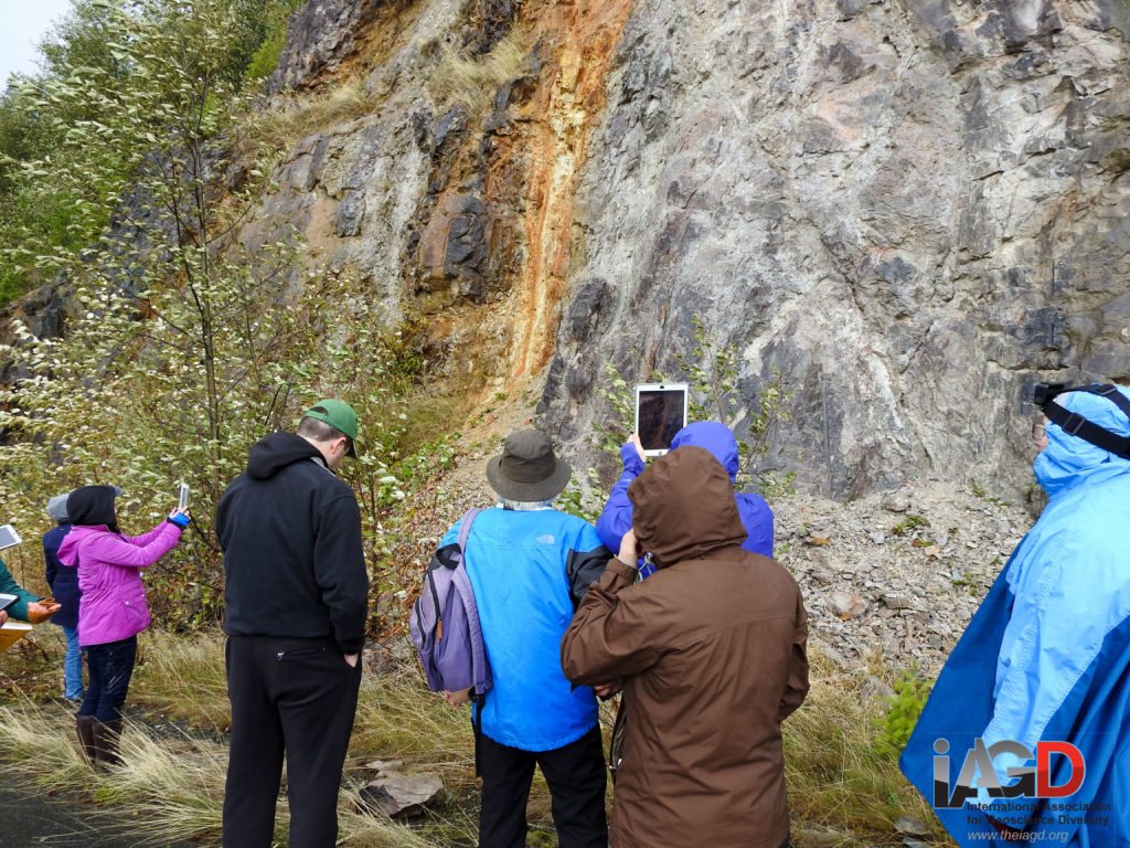 People in raincoat take photos and videos of a gray and orange colored rock wall.