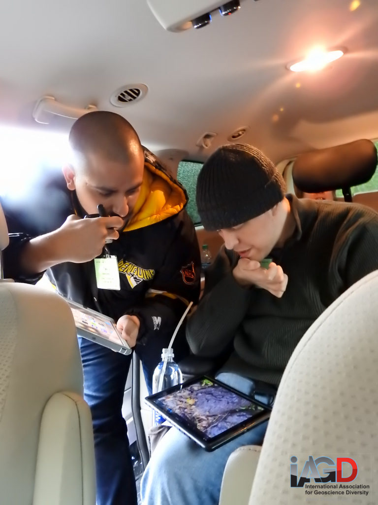 Two people, one crouching and one in a wheelchair, in a van study video on an iPad and talk to field trip participants at the outcrop using a hand radio.