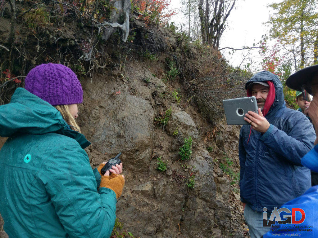 A person in a green coat and purple hat talks into a hand radio while a man, facing her holds an iPad to record video. They are standing in front of a muddy outcrop with boulders sticking out of it.