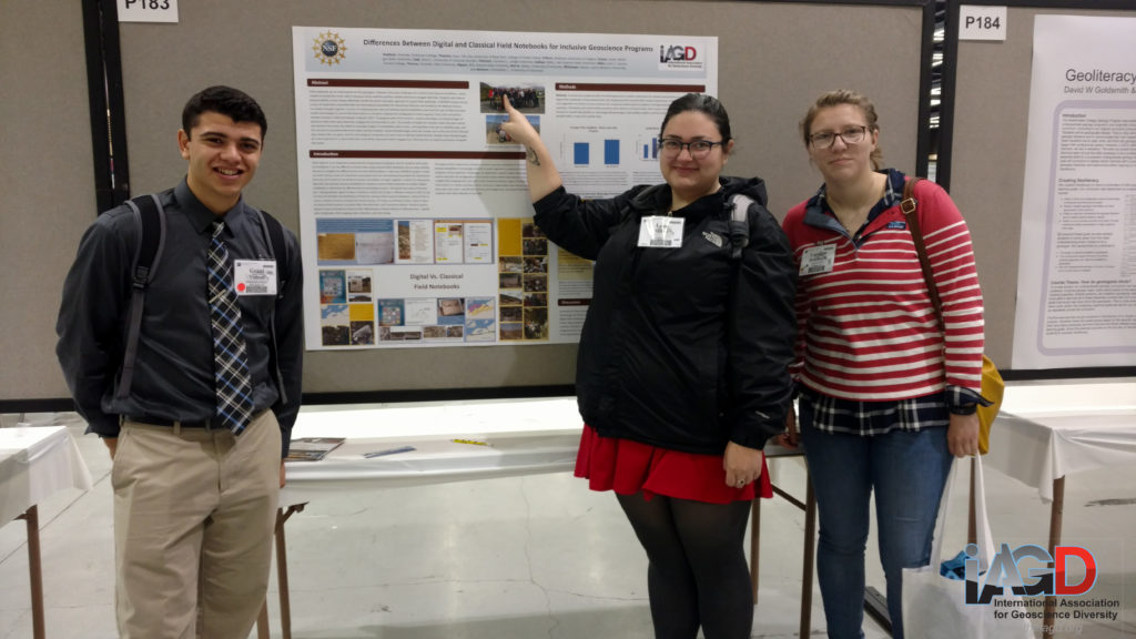 Three students stand in front of their poster, one points to herself in a photo on the poster.