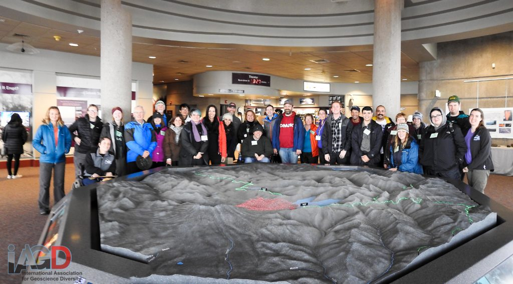 A group of 30 people stand and sit behind a large indoor 3D model of Mount Saint Helens.