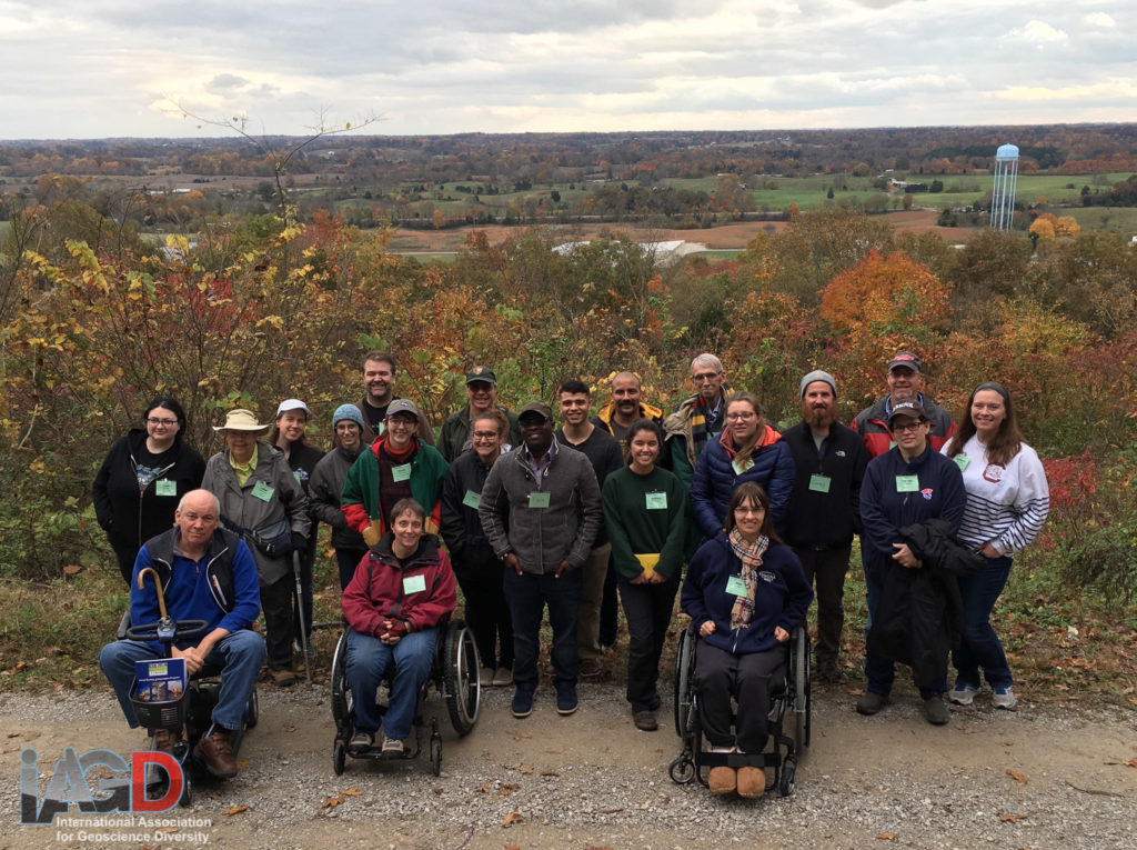 21 people stand or sit in wheelchairs in front of fall foliage and an overlook of a valley.