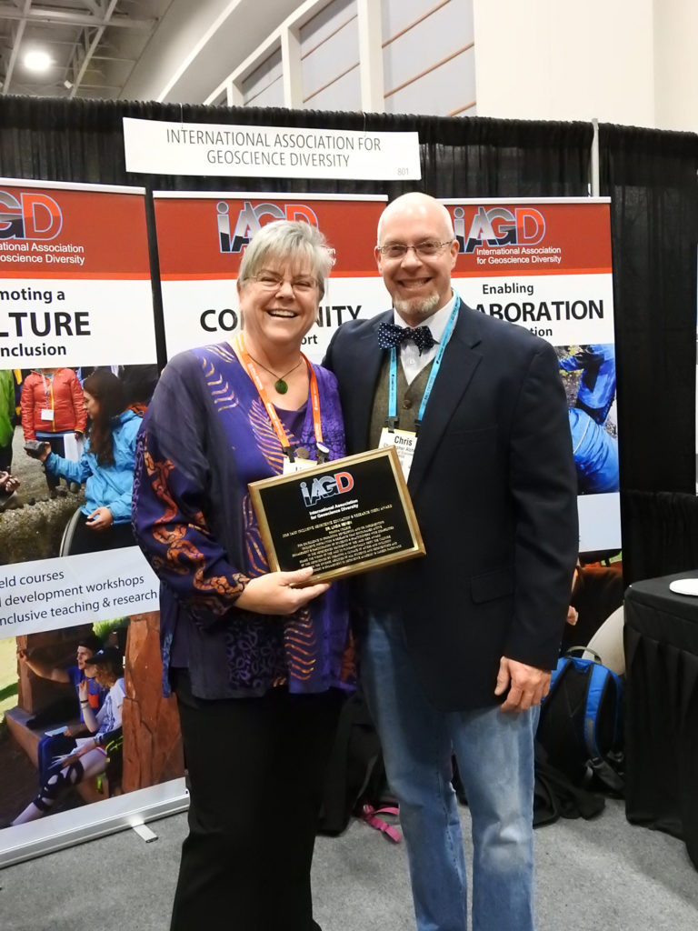 Linda Reinen and Chris Atchison stand in front of the IAGD booth holding a plaque