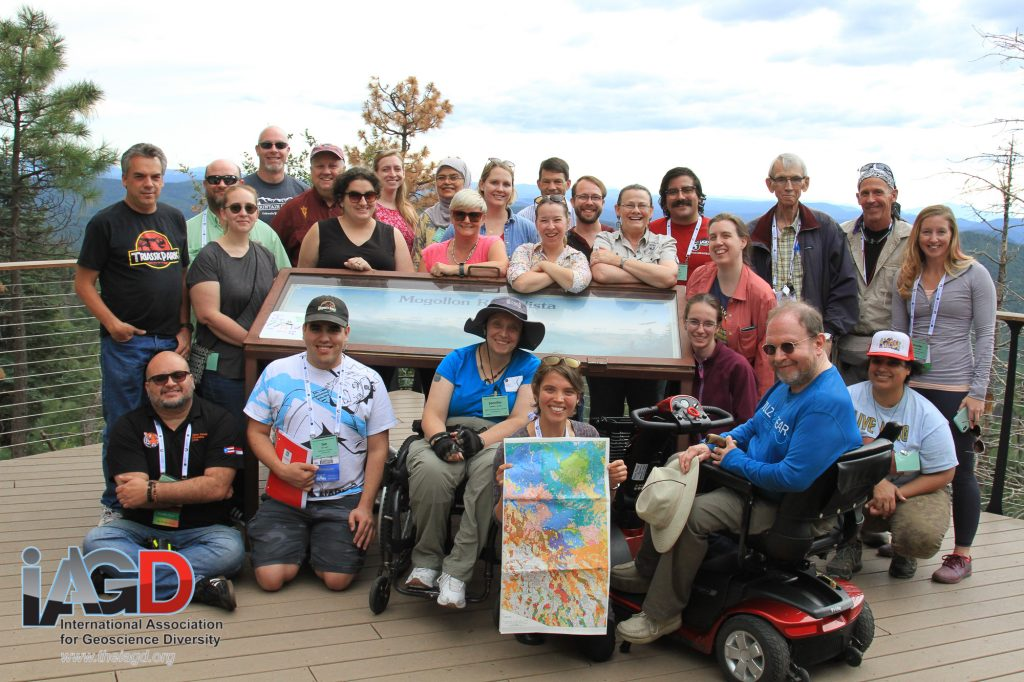 Field trip participants gather around an interpretive sign at an overlook in Arizona with rolling blue hills and pine trees in the background.
