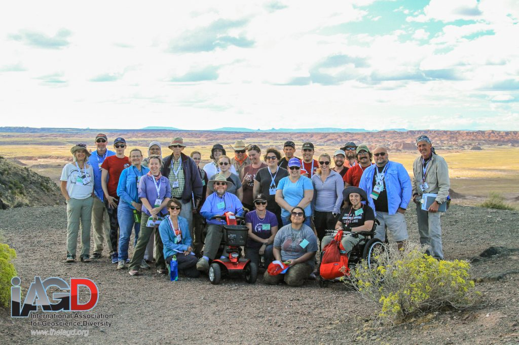 Field trip participants on a gravel overlook with a long desert vista in the background.