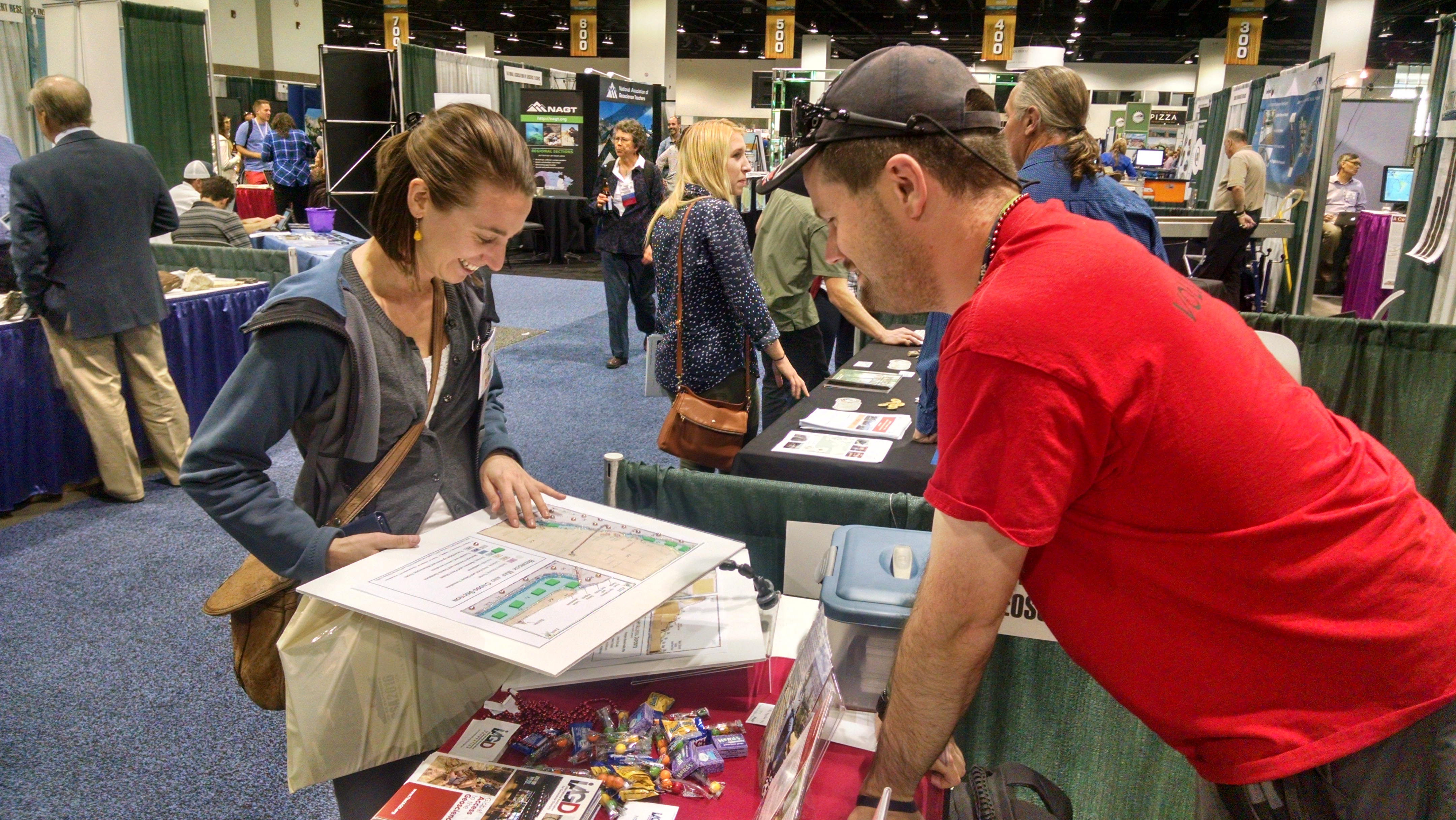 Cole shows a map to a conference attendee at the IAGD booth in the expo hall.